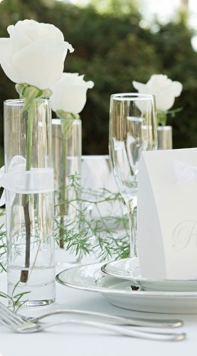 Table set with white tablecloth, full plating and three vases with white ribbon tied around the center and a single white rose sitting inside