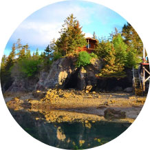 Circular image of a building on a forested cliff about the shore and water