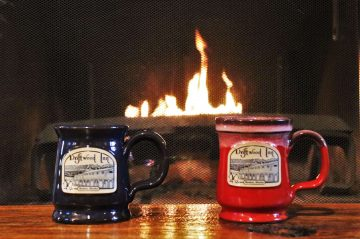 red and blue mugs sitting on table in front of fireplace