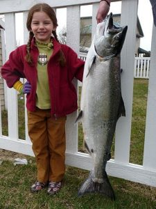 girl standing next to fish