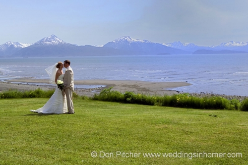 Bride and groom on meadow before the bay
