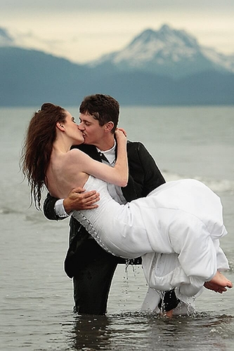 Bride carried bridal style by groom in water