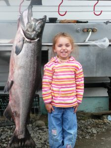 little girl posing with hanging fish