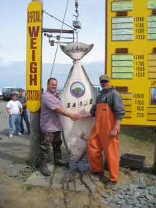 men shaking hands in front of hanging fish