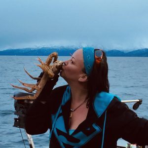 Woman kissing Tanner crab with ocean in the background