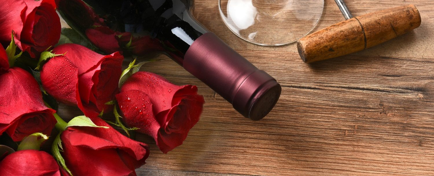 A wine bottle with red roses and a glass and cork screw on a rustic wood table.