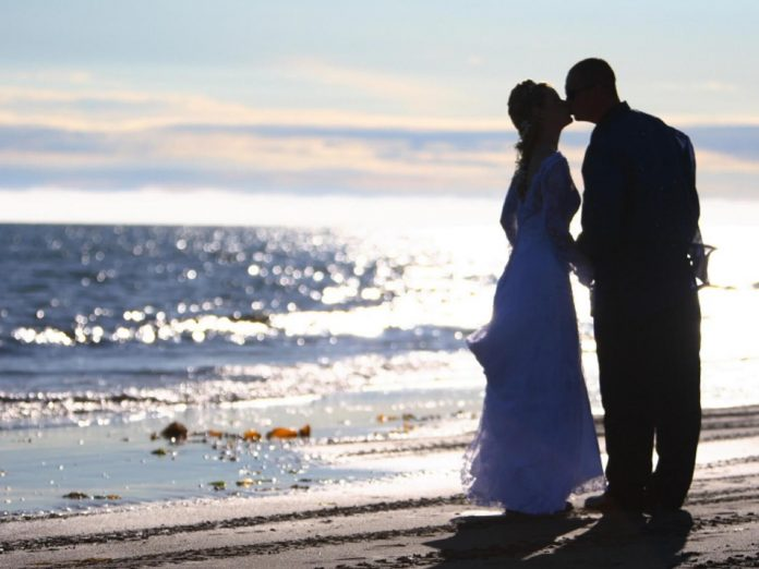 Couple kissing in wedding attire on Bishop's Beach.