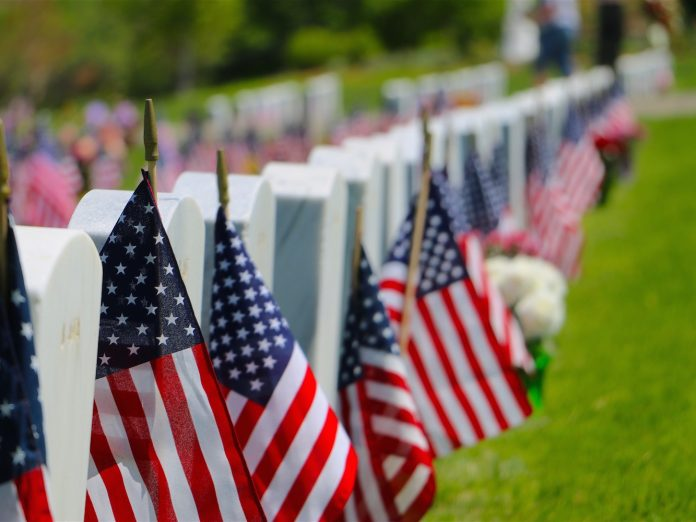 White headstones in a cemetery decorated with American flags