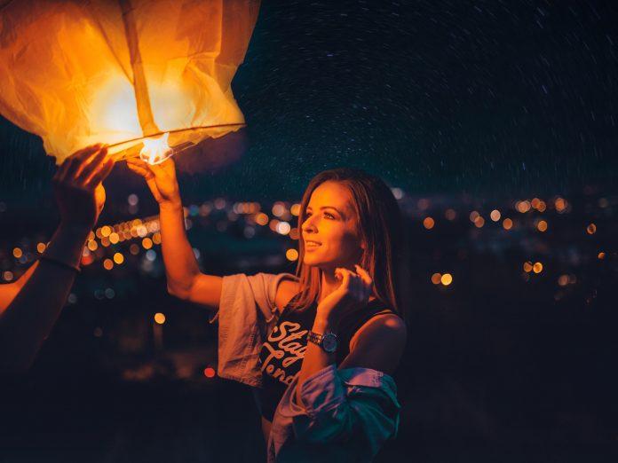 Woman lighting paper lantern.