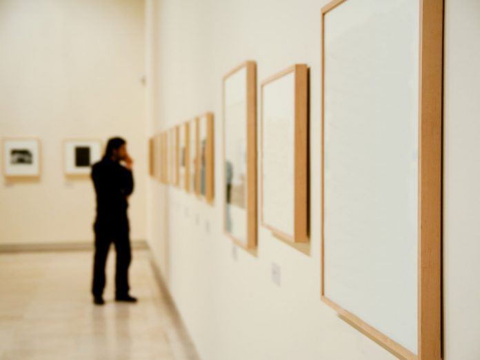 Person looking at framed art at a gallery.