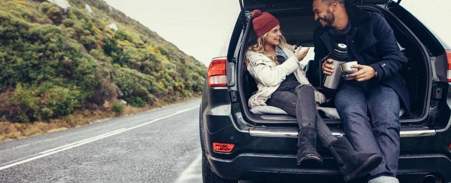 Couple sitting in the back of an SUV with the trunk open. Stopping on a road trip.