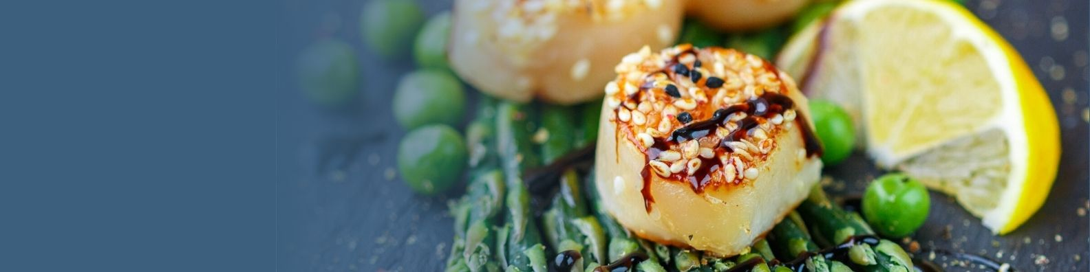 Scallops on a bed of peas and asparagus with lemon
